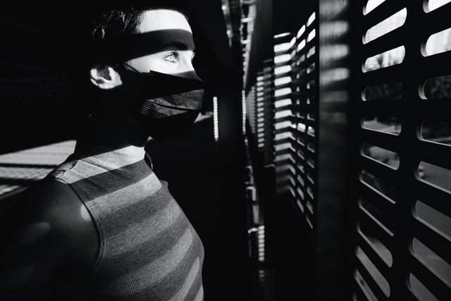 woman in a dark room with a dark mask looking through blinds at the light outdoors